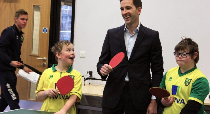 Adam Drury plays table tennis with young children
