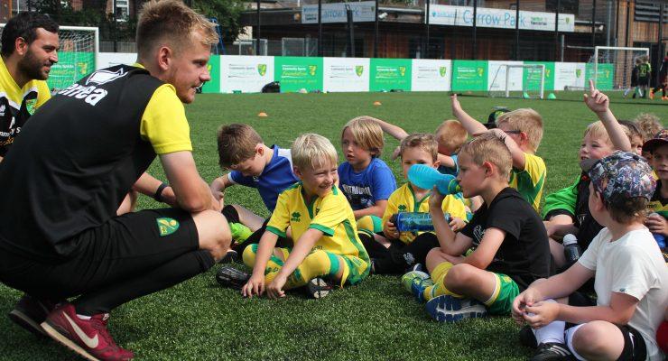 coach speaks to mini kickers children