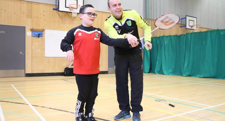 coach with thinning hair teaches young boy badminton