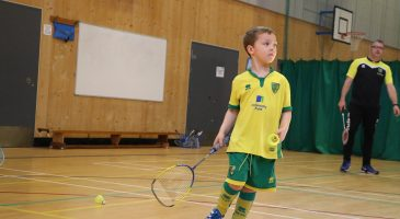 young boy plays badminton