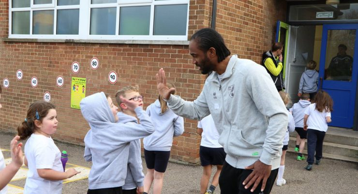 Cameron Jerome high fives a child